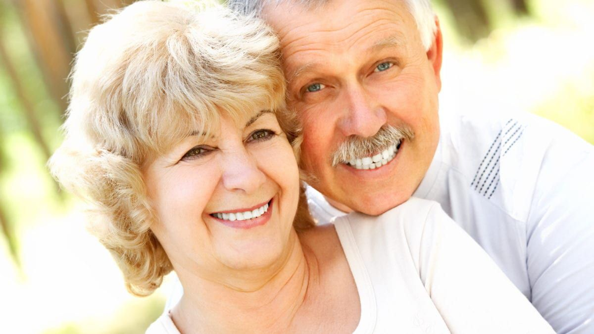 Elderly Couple With Bright Smiles From Dentures