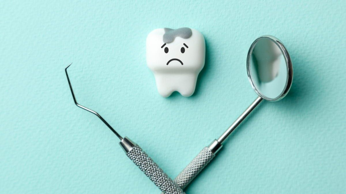 Repaired Tooth Between Dental Tools