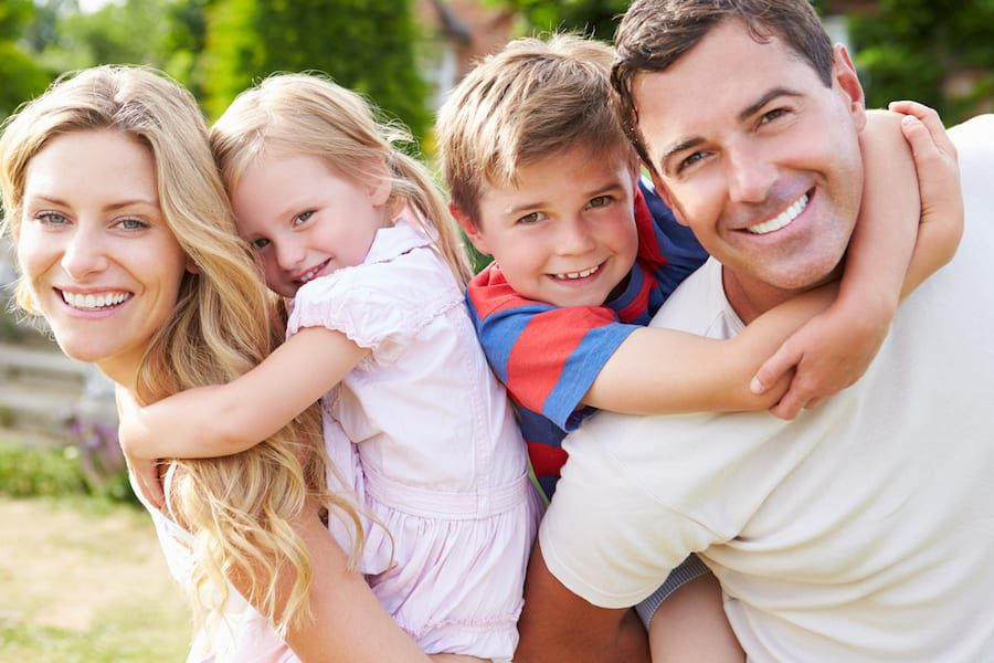 Family Smiling together, man with his wife, son, and daughter at the park