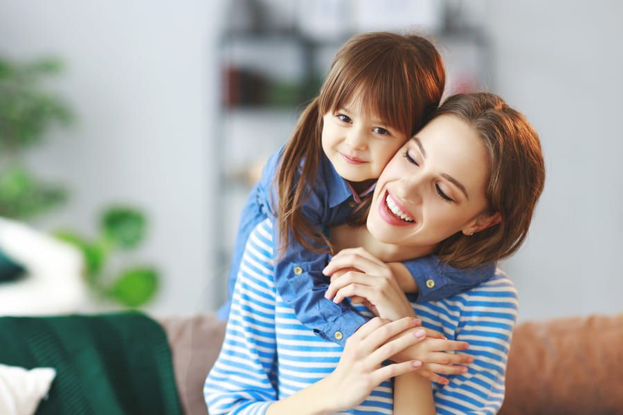 Women wearing striped blue shirt smiling with her daughter also wearing blue