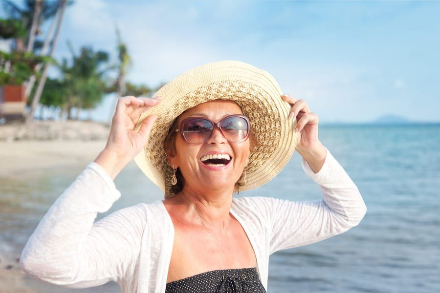 Older lady smiling at the beach wearing sunglasses and a beach hat