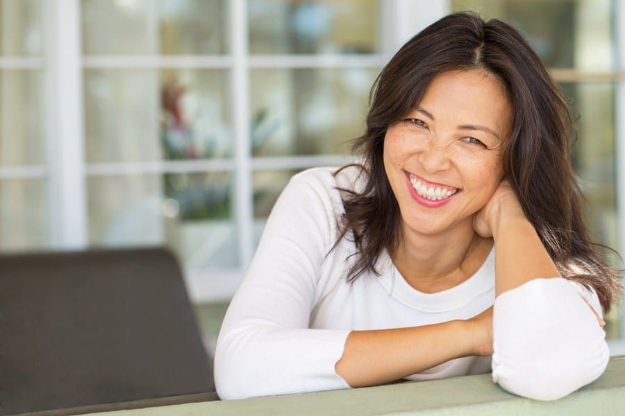 female smiling while sitting on desk