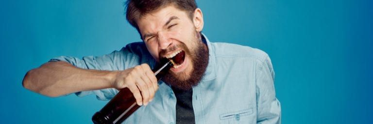 Man opening alcohol with teeth
